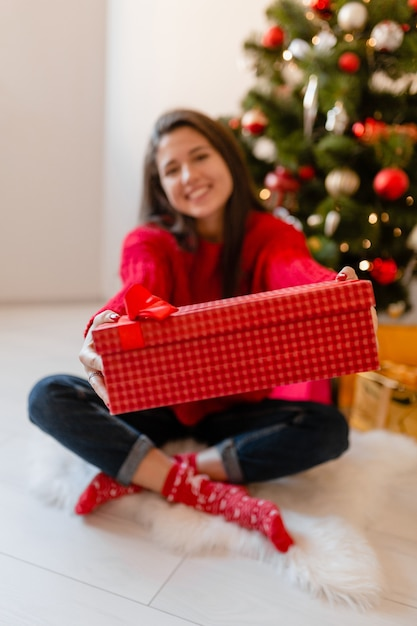 선물과 선물 상자를 풀고 크리스마스 트리에 집에 앉아 빨간 스웨터에 흥분된 예쁜 여자를 웃고 무료 사진