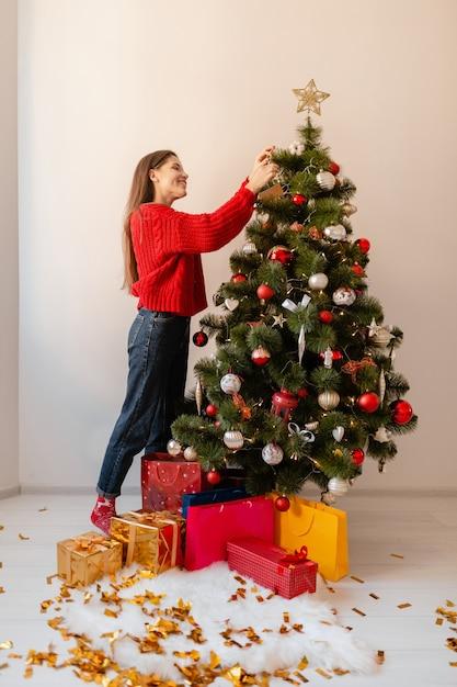 선물 및 선물 상자로 둘러싸인 크리스마스 트리를 장식하는 집에 서있는 빨간 스웨터에 웃는 흥분된 예쁜 여자 무료 사진