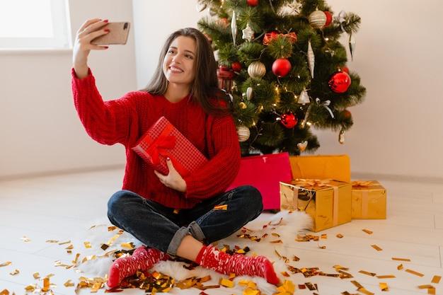 Sorridente donna graziosa eccitata in maglione rosso seduto a casa all'albero di natale disimballaggio regali e scatole regalo prendendo selfie foto sulla fotocamera del telefono Foto Gratuite