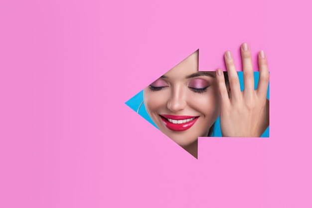 Smiling face of a beautiful model with bright eye make-up and bright pink lips on carved purple figure in the form of an arrow to the left posing in profile Premium Photo
