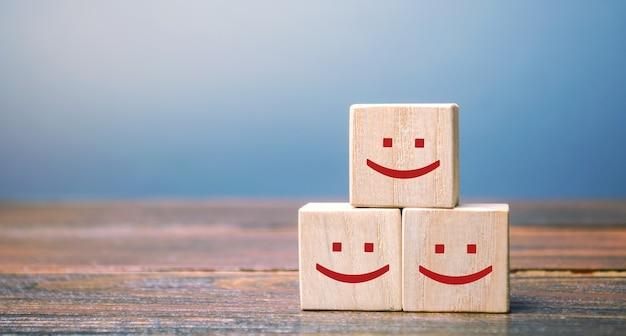 Улыбающиеся лица на деревянных блоках. Premium Фотографии