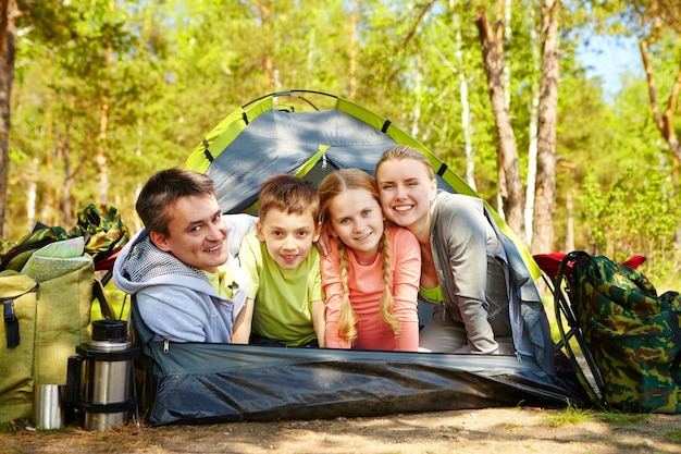 Smiling family in the tent on sunny meadow Free Photo