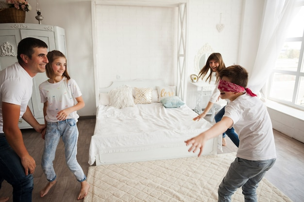 Smiling family playing blind man's buff in bedroom Free Photo