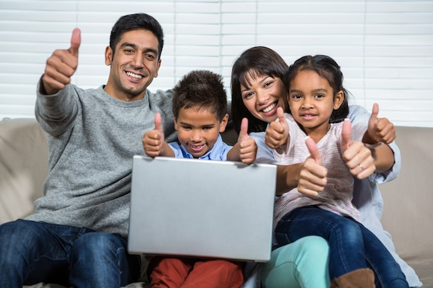 Smiling family on the sofa showing their thumbs up Premium Photo