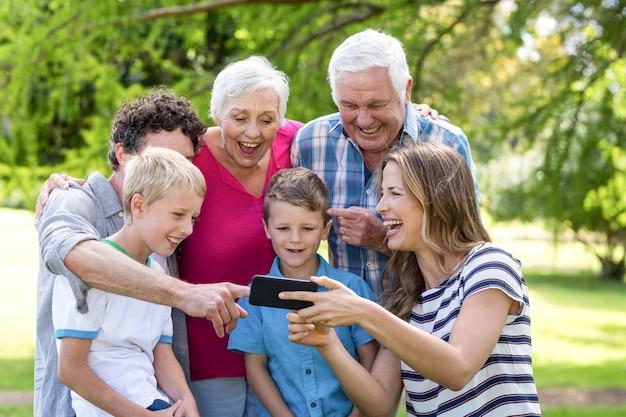 Smiling family using smartphone Premium Photo