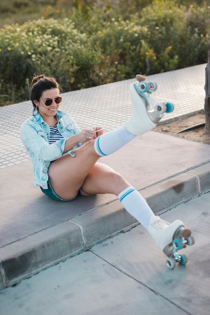 Smiling fashionable young woman pulling the roller skate lace Free Photo