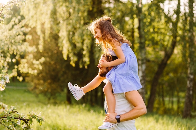 Smiling father carrying her daughter on shoulders Free Photo