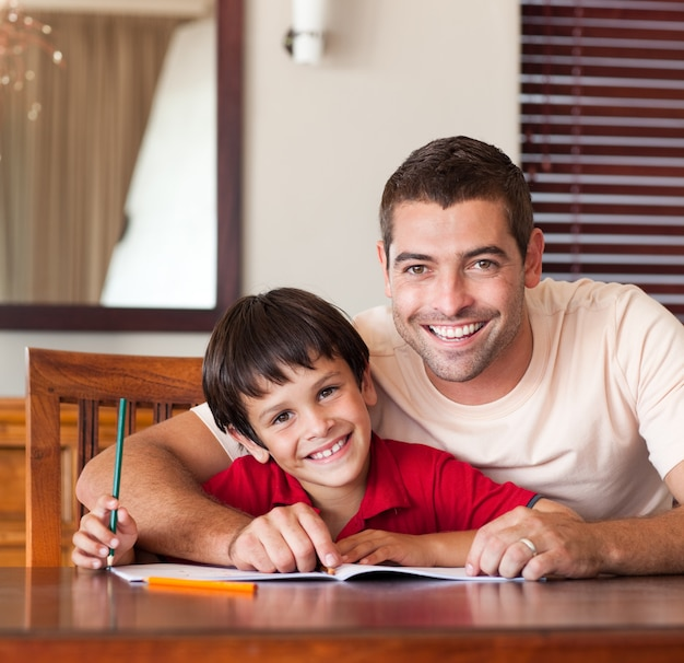 Smiling father helping his son for homework Premium Photo