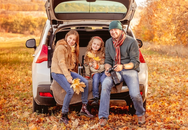 Smiling father with daughters in autumn surroundings Premium Photo