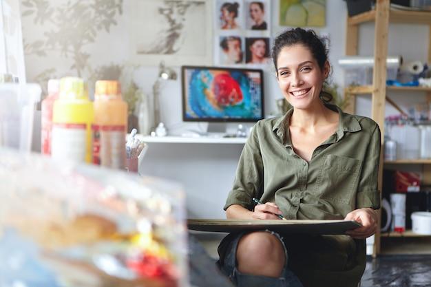 Sorridente artista femminile che indossa abiti casual seduto nel suo gabinetto con schizzi e vernice colorata, avendo espressione felice pur essendo felice di creare una bella immagine. pittore che lavora in officina Foto Gratuite