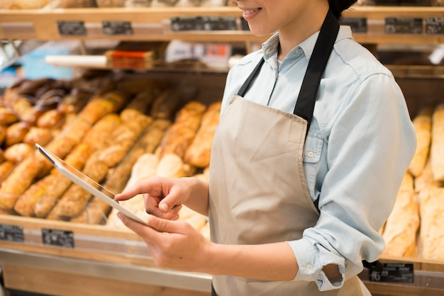 Smiling female bakery seller surfing tablet against different pastry Free Photo