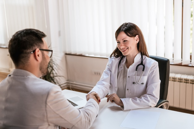 Smiling female doctor at the clinic giving an handshake to her patient Premium Photo