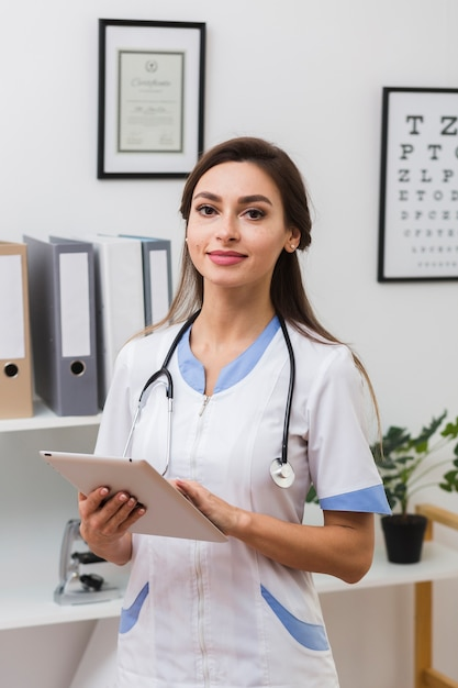 Smiling female doctor holding a folder Free Photo