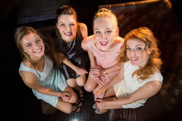 Smiling female friends sitting together in sofa at bar Premium Photo