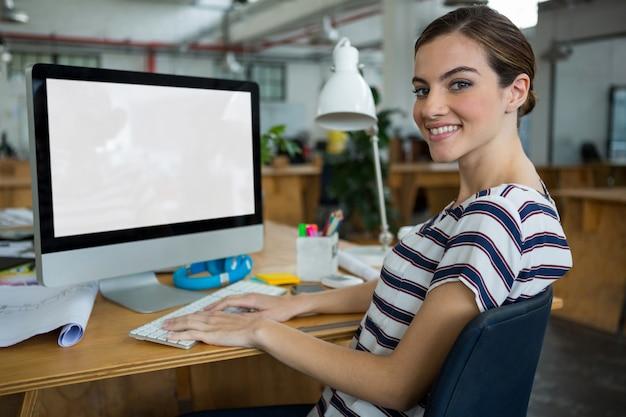 Smiling female graphic designer working on computer Premium Photo