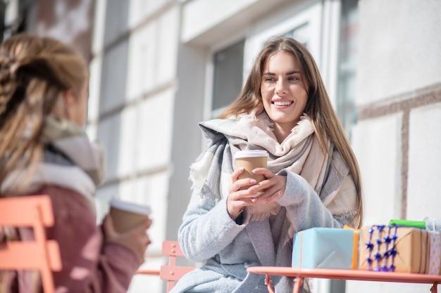 사춘기 소녀와 함께 야외 카페에 앉아 커피 컵을 들고 웃는 여성 프리미엄 사진