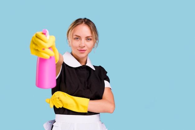 青い壁に立っているカメラを見てピンクのスプレーボトルを示す笑顔の女性用務員 Premium写真