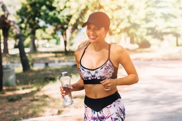 Smiling female jogger running with water bottle in the park Free Photo