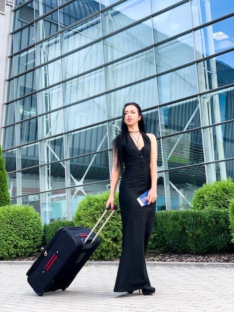 空港からスーツケースを引いて進む女性の乗客の笑顔 Premium写真
