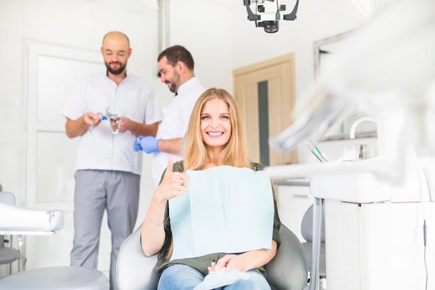 Улыбаясь женского пациента gesturing ок знак перед двумя мужчинами стоматолога Бесплатные Фотографии