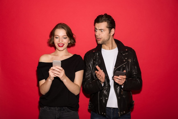 Smiling female punk using smartphone while man peeps at him Free Photo