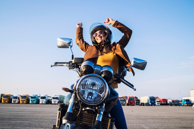Smiling female rider sitting on her motorcycle with arms high showing happiness Free Photo