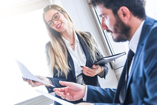 Smiling female secretary showing document to male manager Free Photo