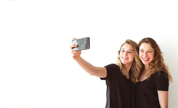 Smiling female sister taking selfie on cellphone against white backdrop Free Photo