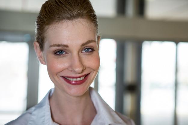 Улыбающийся женский персонал в терминале аэропорта Бесплатные Фотографии