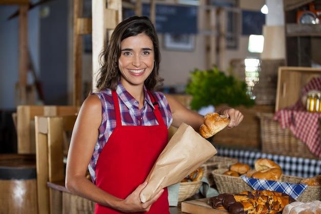 Улыбающийся женский персонал упаковывает сладкую еду в бумажный пакет на прилавке в пекарне Premium Фотографии