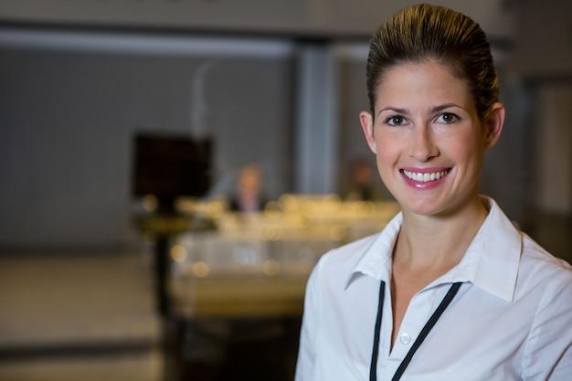 Улыбающийся женский персонал, стоящий в аэропорту Бесплатные Фотографии