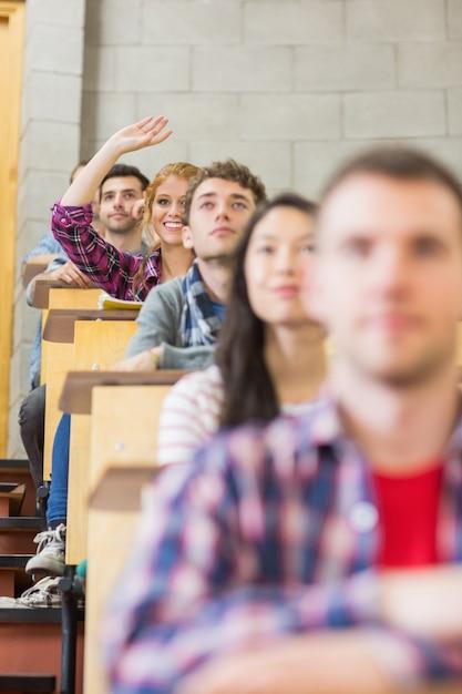 Smiling female student raising hand in classroom Premium Photo