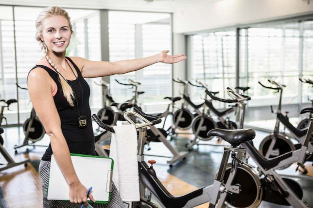Smiling female trainer showing the gym at the camera Premium Photo