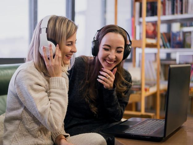 Улыбающиеся женщины в наушниках смотрят на ноутбук Бесплатные Фотографии