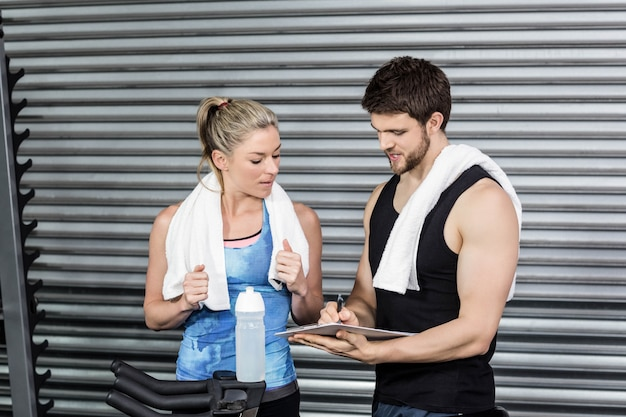 Smiling fit couple taking notes at gym Premium Photo
