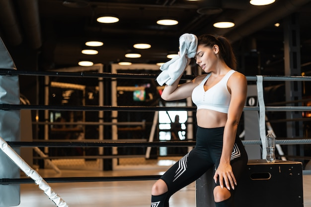 Smiling fit girl holding towel and taking rest in gym. girl wipes sweat with a towel Free Photo