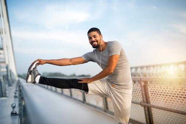 Uomo sportivo in forma sorridente che si riscalda per l'allenamento dell'atleta afroamericano che allunga le gambe prima di correre. Foto Gratuite