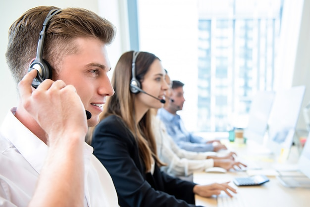 Smiling friendly man working in call center office with team Premium Photo