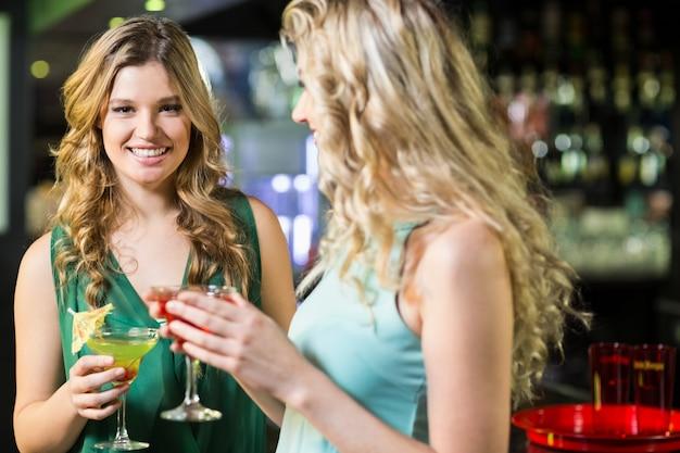 Улыбающиеся друзья пьют коктейли Premium Фотографии