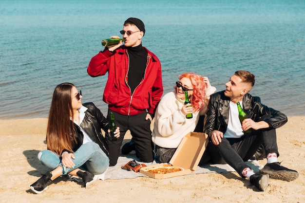 Smiling friends having party on beach Free Photo