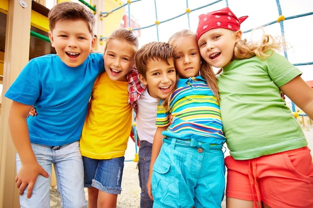 Smiling friends hugging in the playground Free Photo