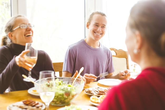 Smiling friends sit at the kitchen table. a joyful group of young people having fun together. Premium Photo