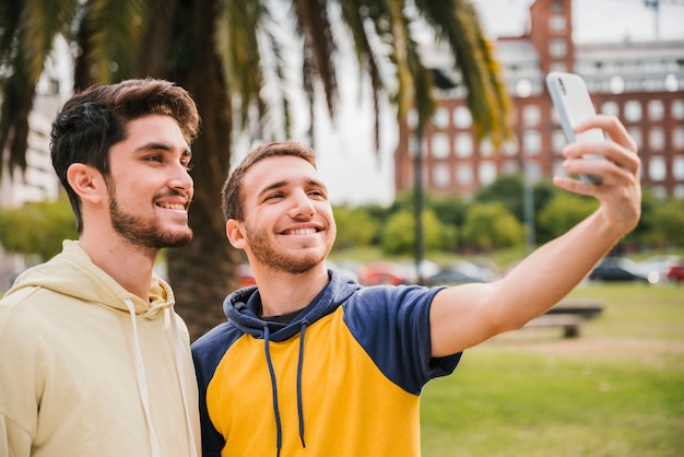 Smiling friends taking selfie in park Free Photo