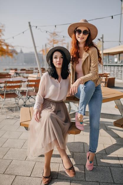 屋外カフェのテーブルに座っているジーンズの生姜の女性 無料写真