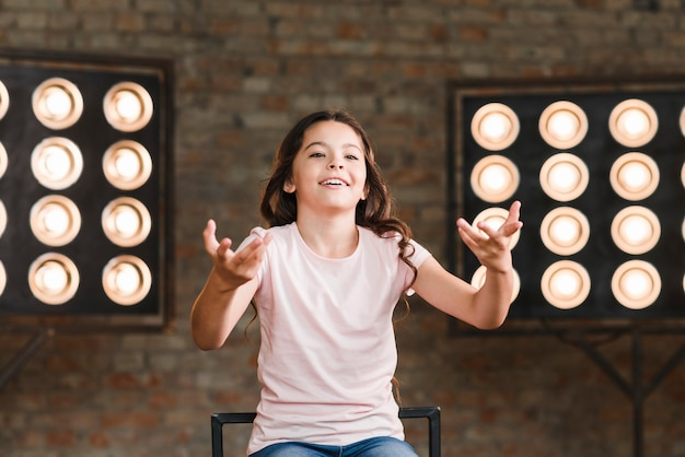Smiling girl acting in studio with stage light in the background Free Photo