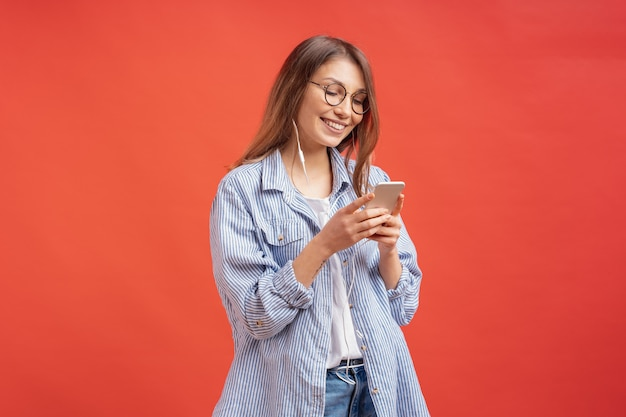 Smiling girl in casual clothes and earphones looking to phone screen Free Photo