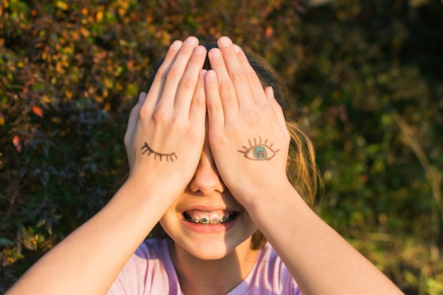 Smiling girl covering their eyes with tattoos on palm Free Photo
