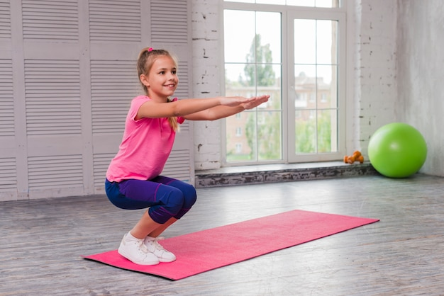 Smiling girl crouching and exercising on pink mat Free Photo