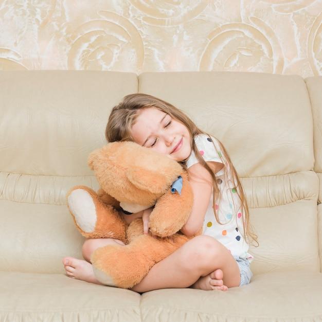 Smiling girl cuddling her teddy bear sitting on sofa Free Photo