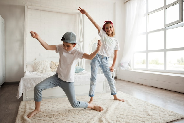 Smiling girl dancing with her little brother at home Free Photo